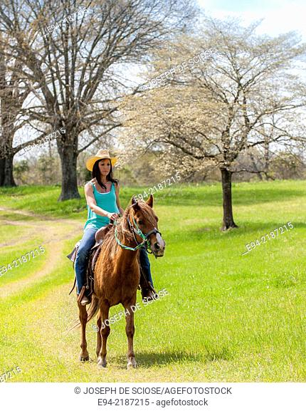 A 36 year old brunette woman wearing jeans and a straw hat riding a horse on a farm