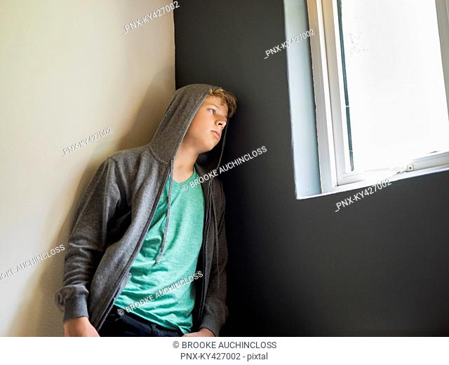 Teenage boy leaning against a wall and thinking