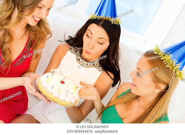 celebration, food, friends, bachelorette party, birthday concept - three smiling women wearing blue hats holding cake with candles