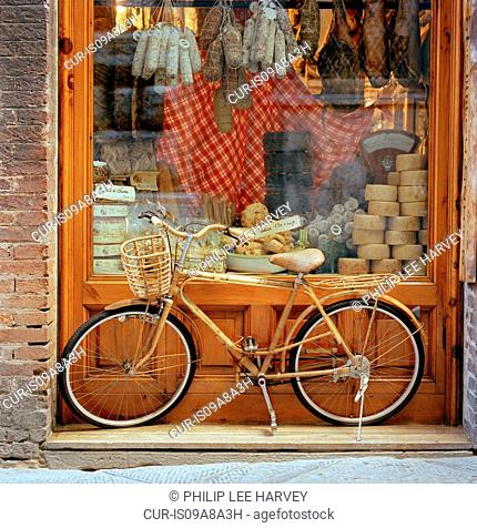 A bicycle stood in front of a shop window in Siena, Tuscany, Italy
