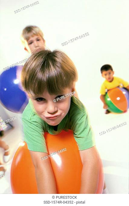 Portrait of three boys playing with rubber balls