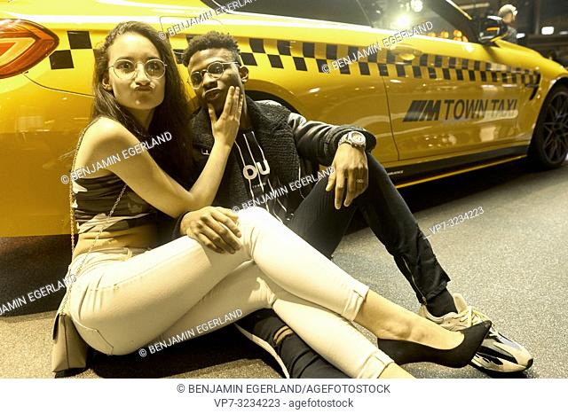 fashionable couple leaning against racing car