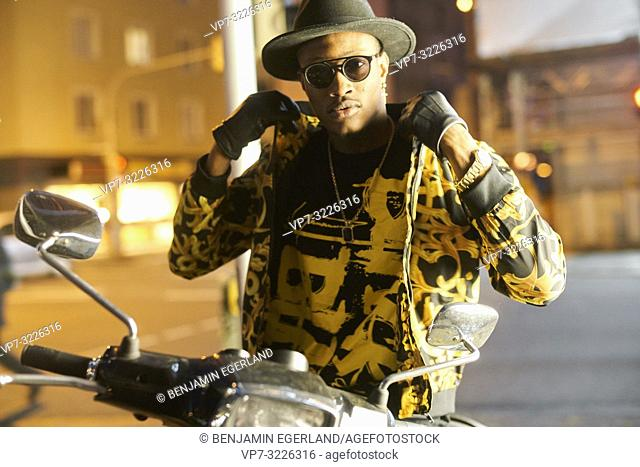 fashion blogger Buckman @sir-bucks, handsome man on bike in city street by night touching collar of fancy outfit, wearing fashionable hat, gloves and sunglasses