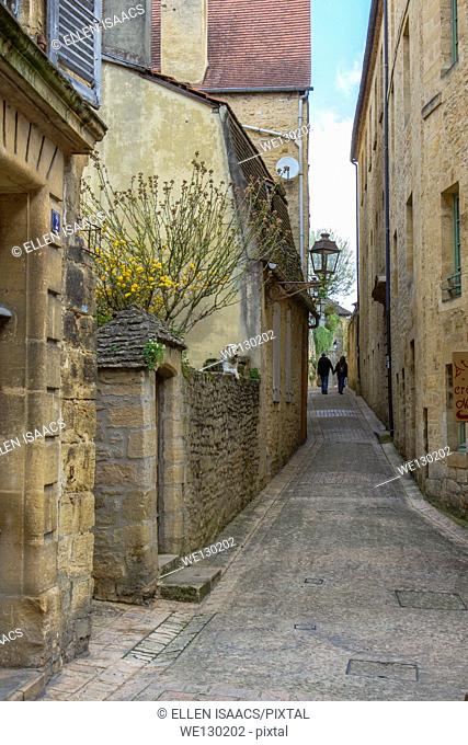 Couple walking hand in hand along narrow cobblestone street among medieval sandstone buildings in charming Sarlat, Dordogne region of France