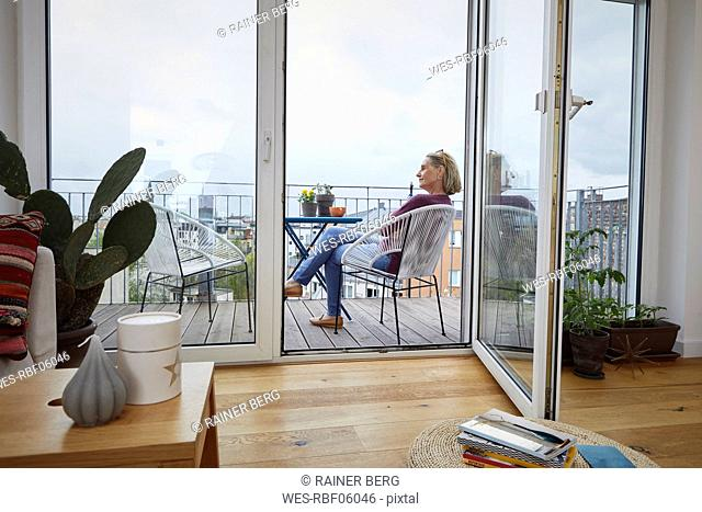 Mature woman at home sitting on balcony