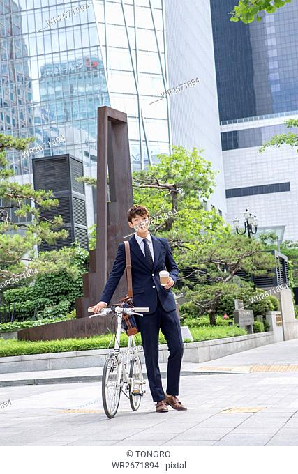 Businessman with takeout coffee and bicycle posing