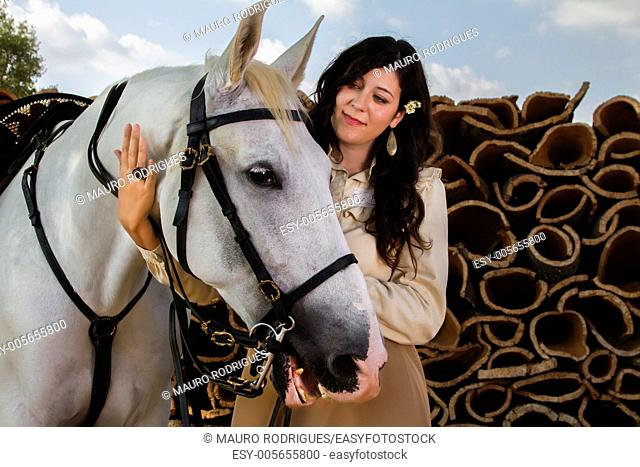 View of a beautiful girl in classic dress with a white horse on the countryside