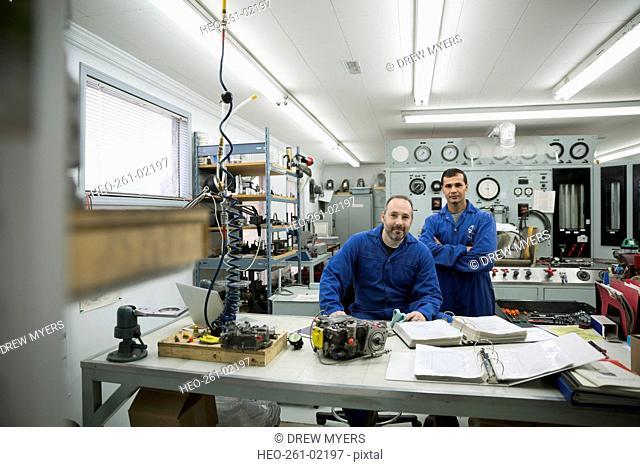 Portrait confident helicopter mechanics in workshop