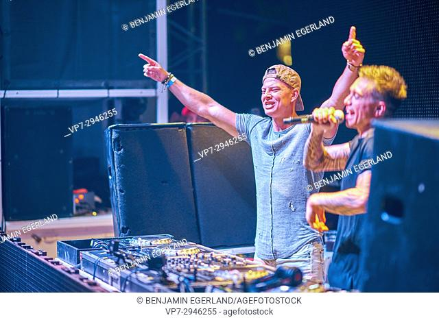 famous Instagrammer and fitness coach 'Student Aesthetics' rising arms next to DJ Headhunterz playing at music festival Starbeach in Hersonissos, Crete, Greece
