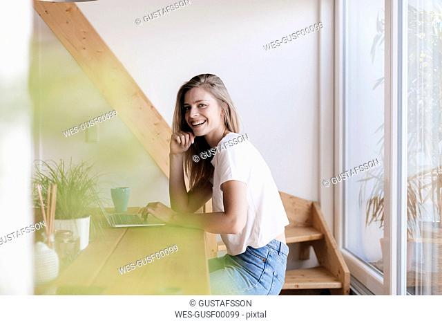 Young woman at home using laptop