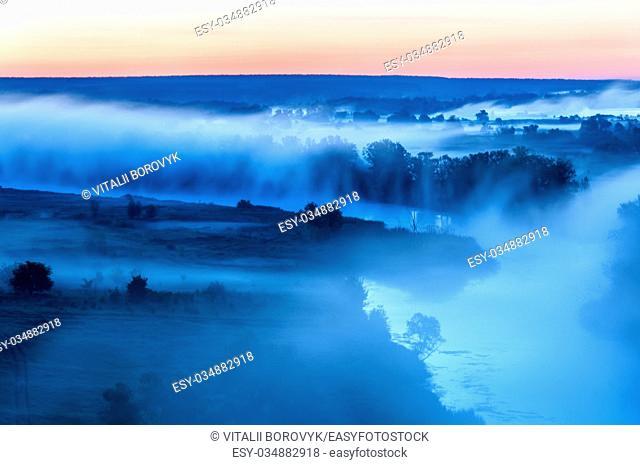 Fog filling the river bed before sunrise