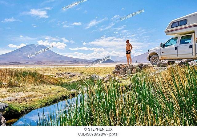 Mature man standing on rock, beside recreational vehicle, looking at view, Salar de Chiguana, Chiguana, Potosi, Bolivia, South America