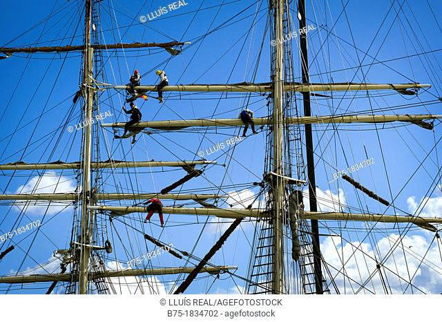 Detail of sailors working on the masts of a vintage yacht