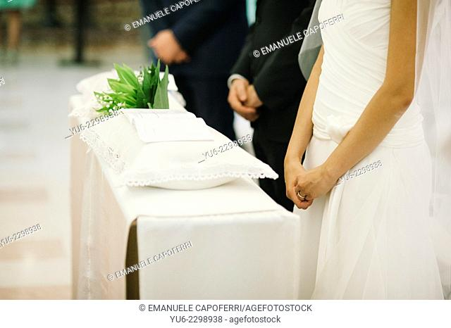Hands of the couple and witnesses in church