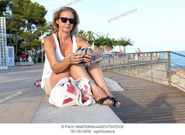 woman looking at cell phone on vacation. Alcocebre. Spain