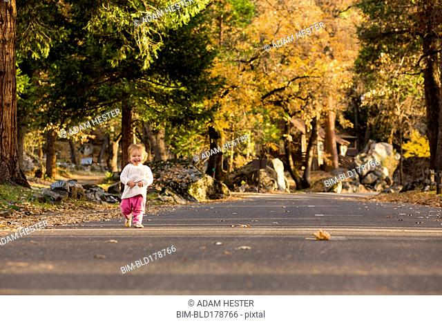 Caucasian baby girl walking on road