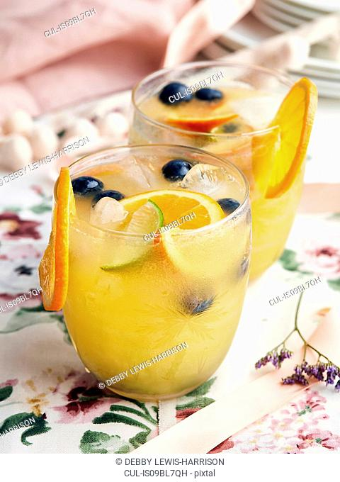 Cocktails with orange slices, berries and ice cubes