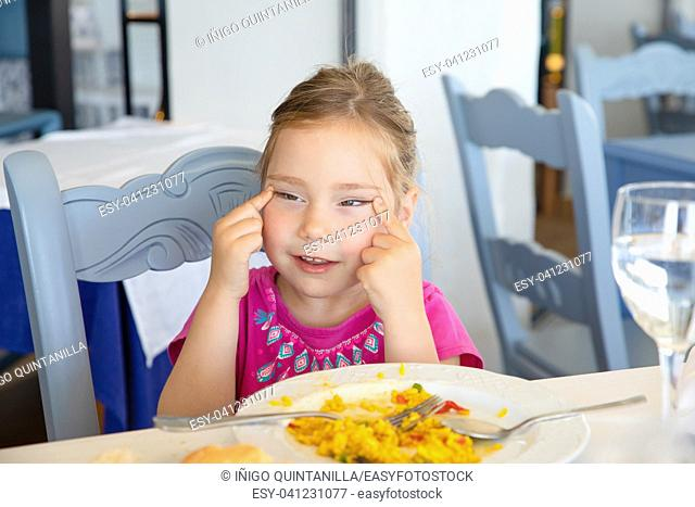 portrait of four years old blonde girl eating Spanish paella rice, making grimaces stretching her eyes, sitting in restaurant