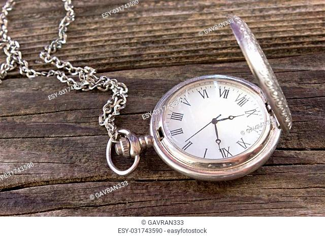 Old pocket watch with chain on wooden background