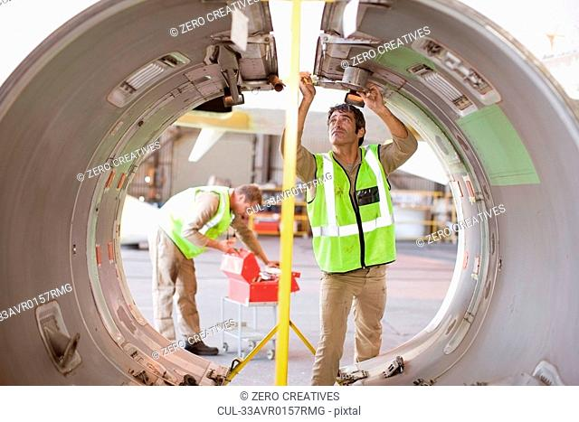 Aircraft workers checking airplane part
