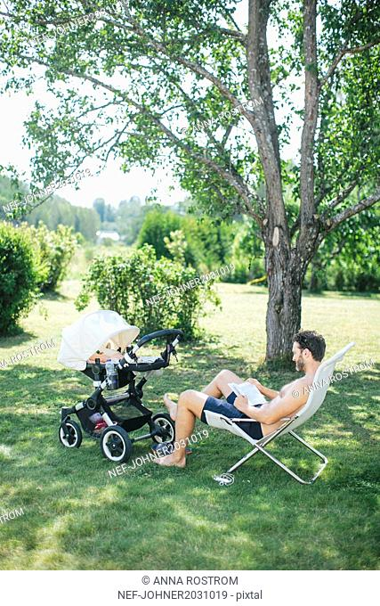 Father in garden with child in buggy