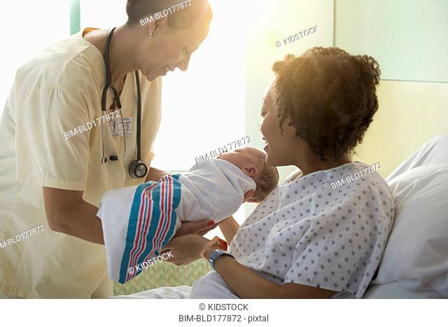 Nurse presenting newborn baby to mother