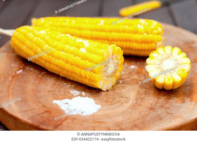 Boiled sweet corn cobs with salt on a wooden background