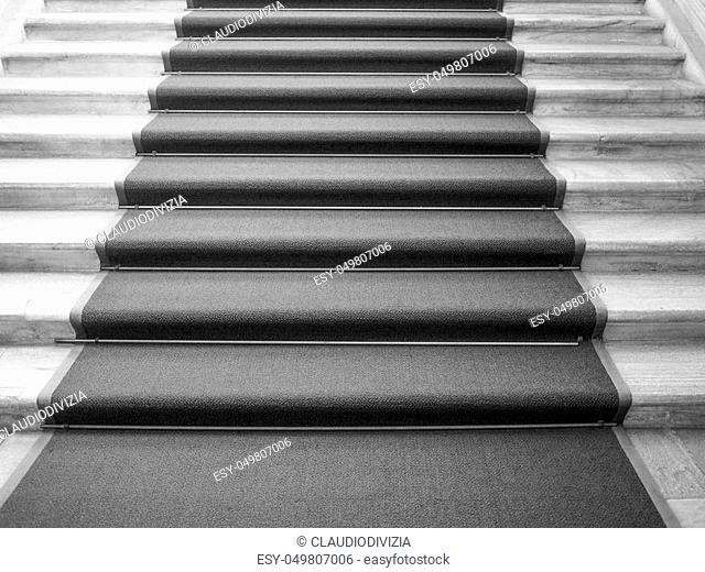 Red carpet on a stairway used to mark the route taken by heads of state, vips and celebrities on ceremonial and formal occasions or events in black and white