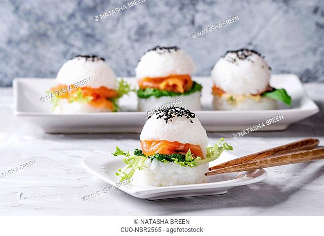 Mini rice sushi burgers with smoked salmon, green salad and sauces, black sesame served on white square plate with wooden chopsticks over gray concrete...