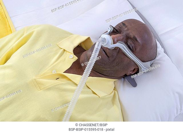 A man wearing a CPAP (Continuous Positive Airway Pressure) mask to treat sleep apnea