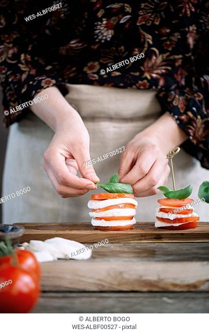 Woman's hands preparing Caprese Salad