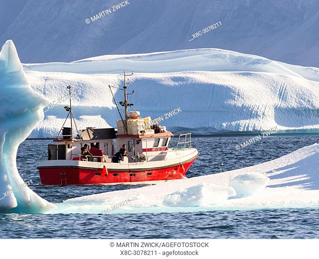 The harbour with typical fishing boats between icebergs. Small town Uummannaq in the north of west greenland. America, North America, Greenland, Denmark