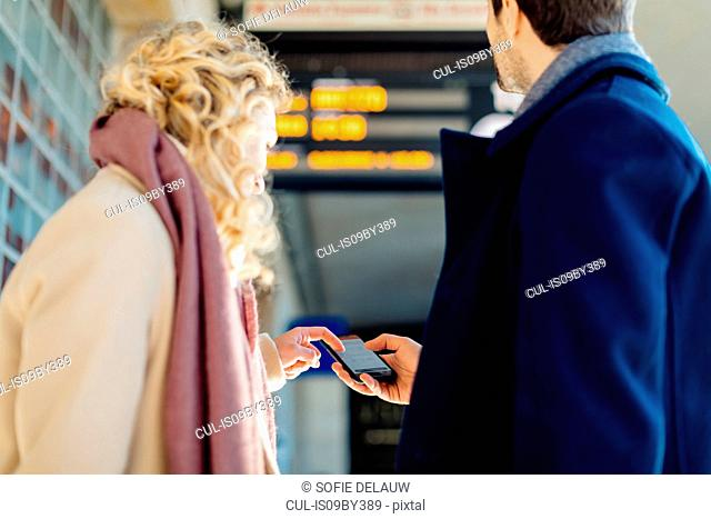 Couple checking smartphone at train station, Firenze, Toscana, Italy