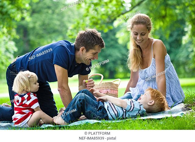Mid adult parents plying with children during picnic