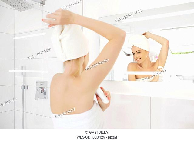 Woman looking at her mirror image while applying deodorant in the bathroom