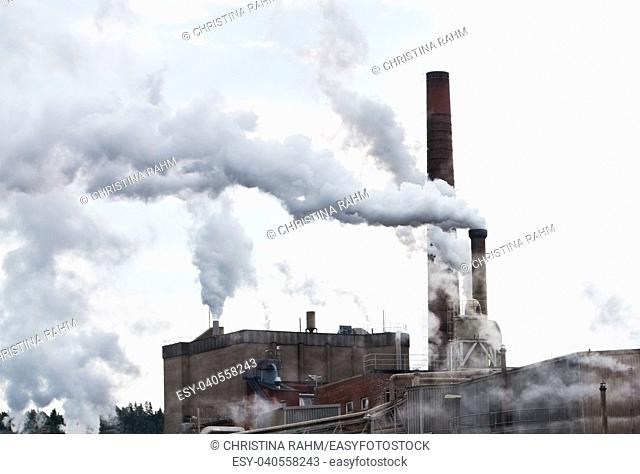 Smoke exhaust pollution through industrial chimneys against gray sky in Sweden. Concept for environment destruction. The image is manipulated (chimney erased)