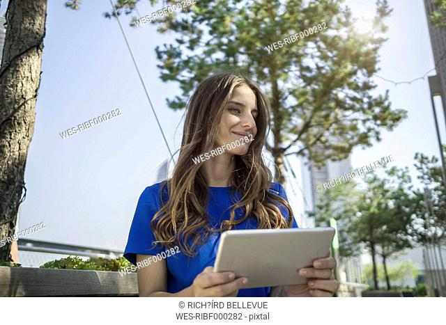Germany, Frankfurt, smiling young woman with mini tablet