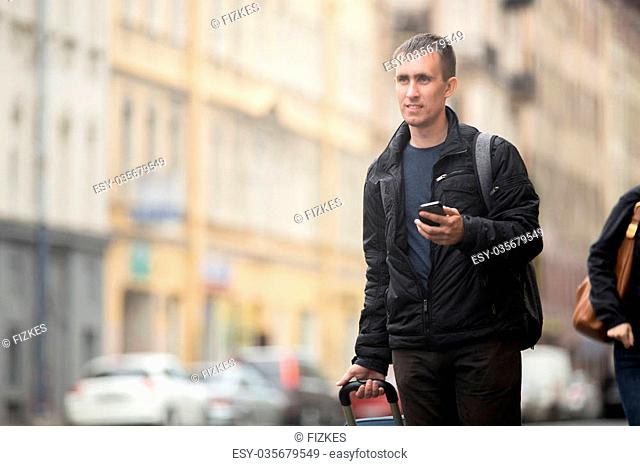 Portrait of young smiling handsome man with luggage bag walking on rainy city street holding cellphone, using app, gps, searching for direction, messaging