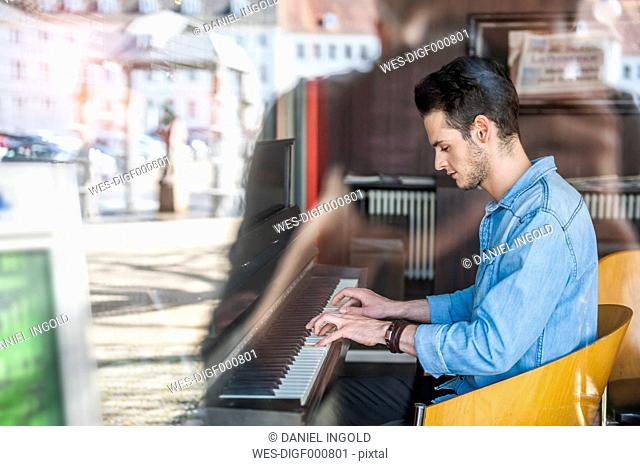 Young man playing piano in a cafe