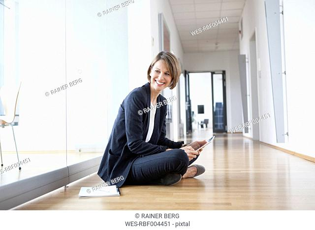 Smiling businesswoman sitting on office floor holding digital tablet