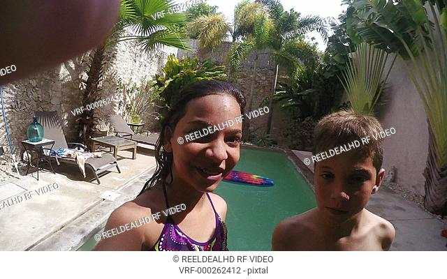 Boy and girl jumping in swimming pool and enjoying