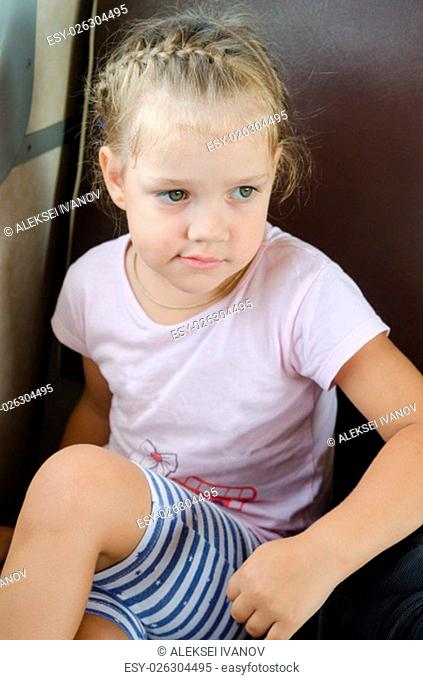 four-year girl sits on a chair in the electric train