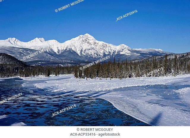 A winter scene on the freezing Athabasca River with Pyramid Mountain in the background in Jasper National Park, Alberta, Canada