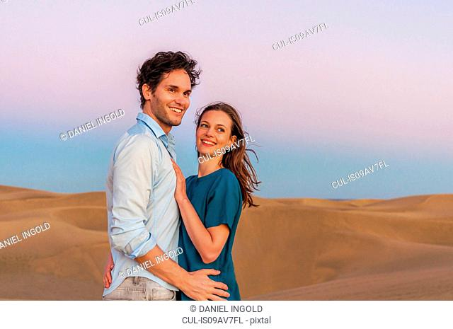 Romantic mid adult couple on sand dunes, Maspalomas, Gran Canaria, Canary Islands, Spain