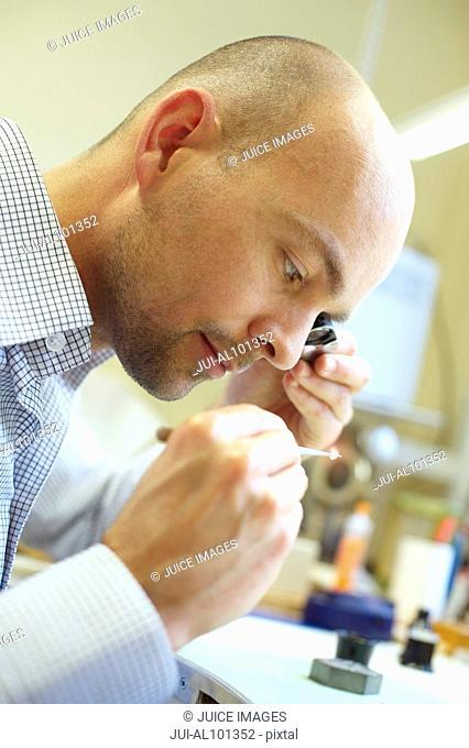 Mid adult man examining diamond in jewelry store