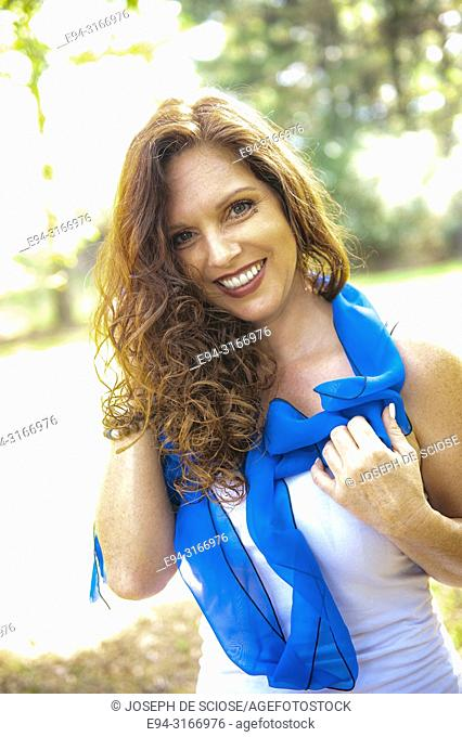 A pretty 39 year old redheaded woman on a country road, smiling at the camera