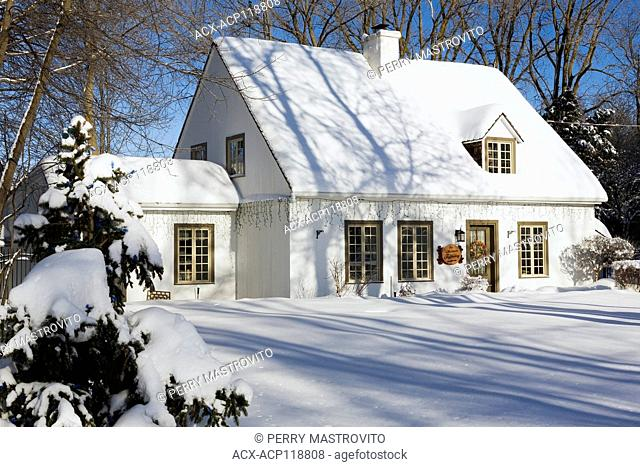 Old circa 1886 white with beige and brown trim Canadiana cottage style home facade with Christmas decorations in winter, Quebec, Canada