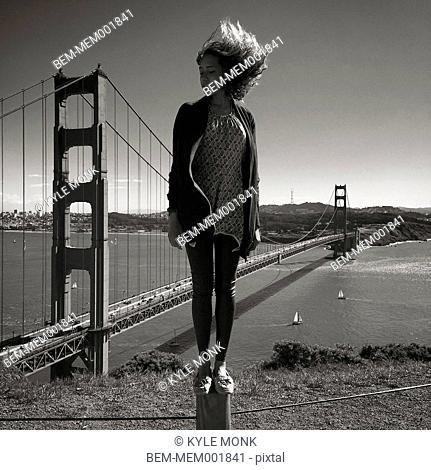 Woman standing over Golden Gate Bridge, San Francisco, California