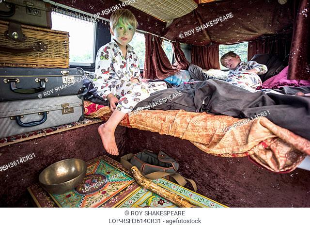 England, Devon, Dartmoor. Two boys having fun in a VW camper van at a festival