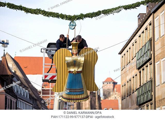 Workers fix the restored tinsel angel 'Baerbel' on to the entrance of the Christkindlesmarkt (lit. Nuremberg christmas market) in Nuremberg, Germany